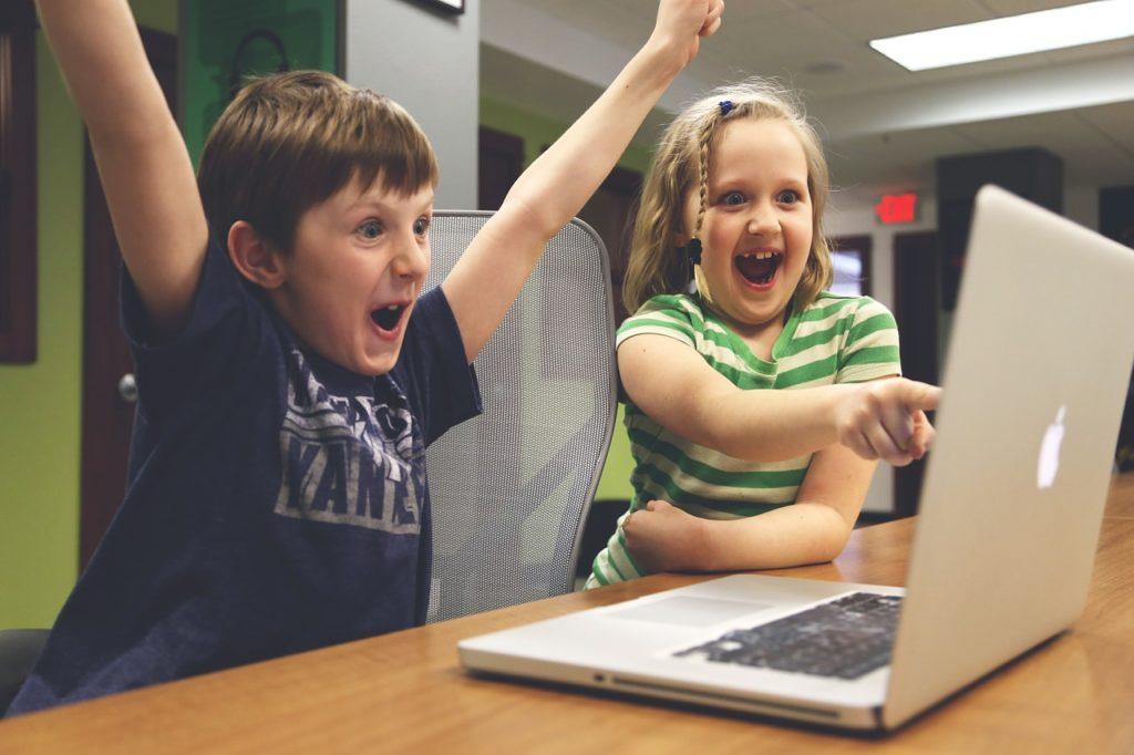 パソコンの前で喜ぶ人